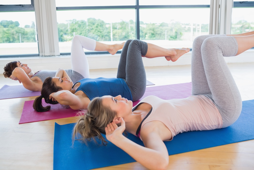 Women doing core exercise on mats in fitness studio
