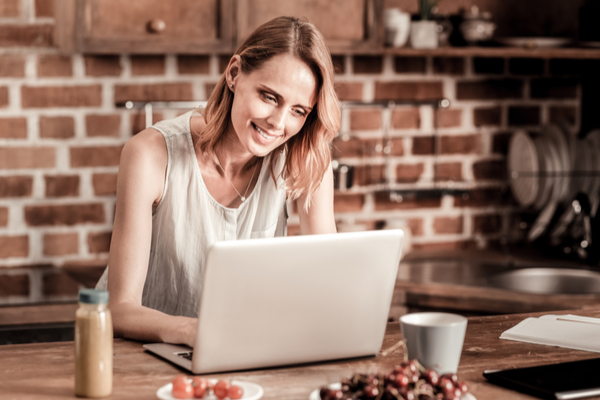 Woman happily working on computer