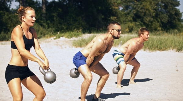 Outdoor fitness training with kettlebells on the beach