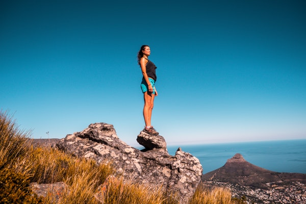 woman-in-black-top-and-blue-shorts-on-stone-under-blue-sky-920038